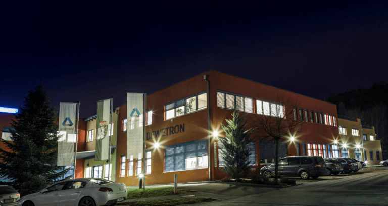 Front view of the building of DEWETRON headquarters in Grambach Austria by night